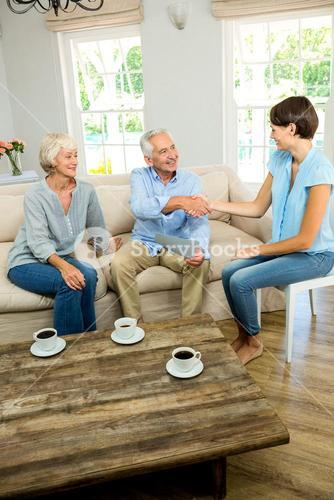 Happy senior couple with female consultant at home