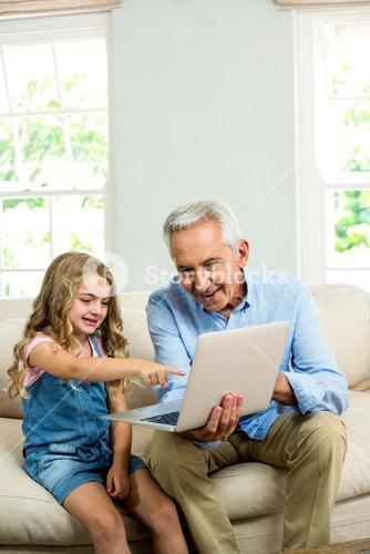 Girl pointing at laptop while sitting with granddad