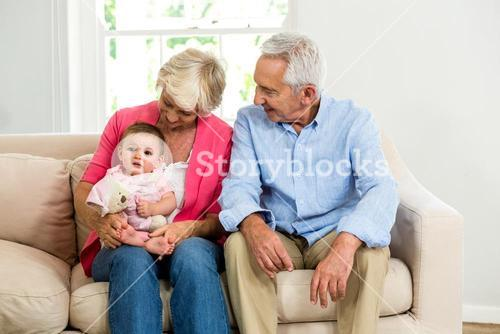 Happy grandparents looking at baby while siting on sofa