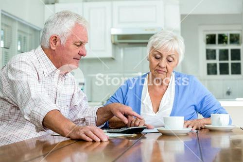 Senior couple with documents while sitting at table