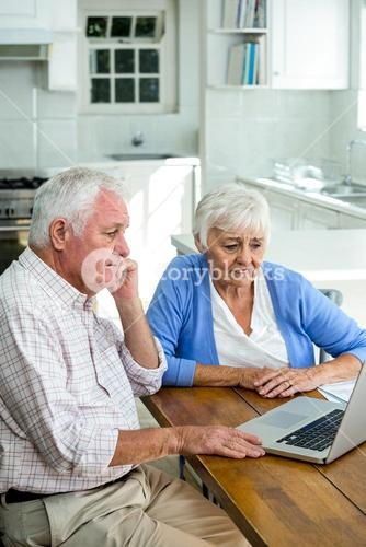 Serious retired couple using laptop