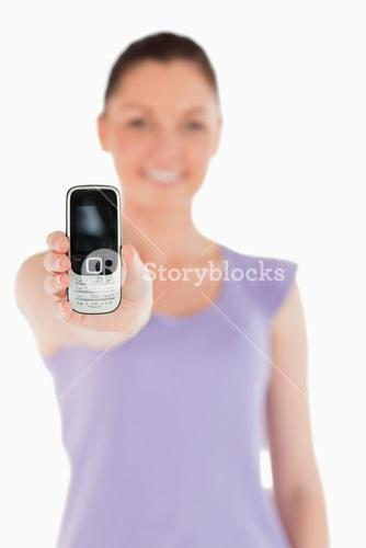 Beautiful woman holding and showing her phone while standing