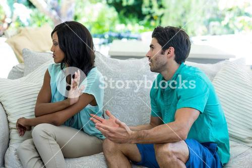 Young couple arguing on sofa
