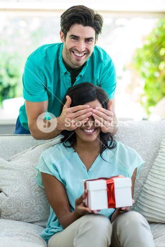 Man giving a surprise gift woman
