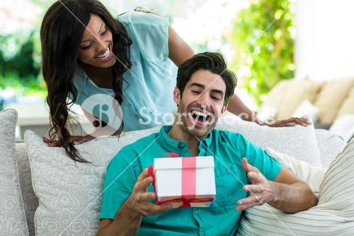 Woman giving a surprise gift to man