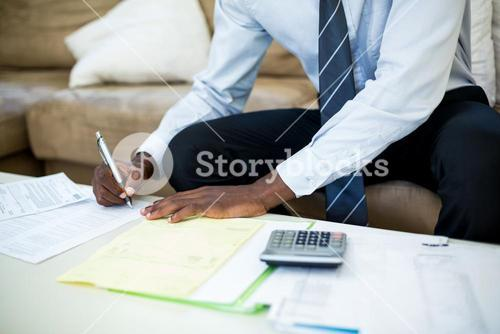 Mid-section of man sitting on sofa and accounting the bills