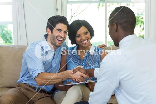 Happy couple shaking hands with real estate agent