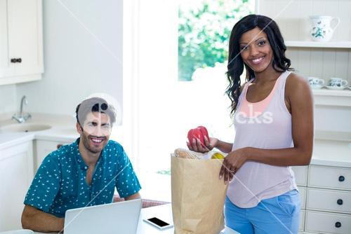 Woman standing with a bag of groceries