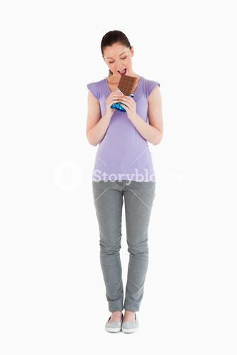Good looking woman eating a chocolate block while standing
