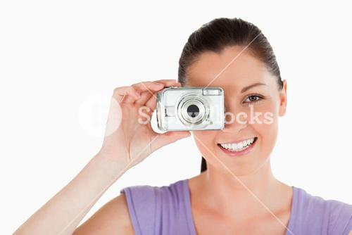 Portrait of an attractive woman using a camera while standing