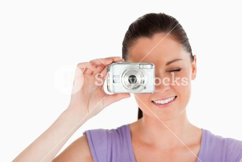 Portrait of a beautiful woman using a camera while standing