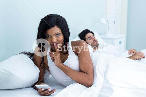 Woman checking her mobile phone while sleeping on bed
