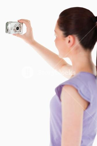 Pretty woman using a camera while standing