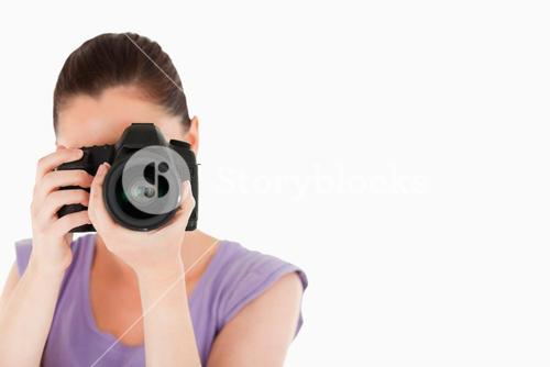 Beautiful female using a camera while standing