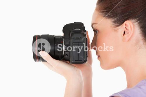 Attractive female using a camera while standing