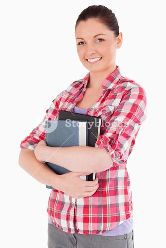 Beautiful female posing with books while standing