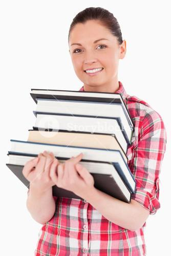 Charming female posing with books while standing