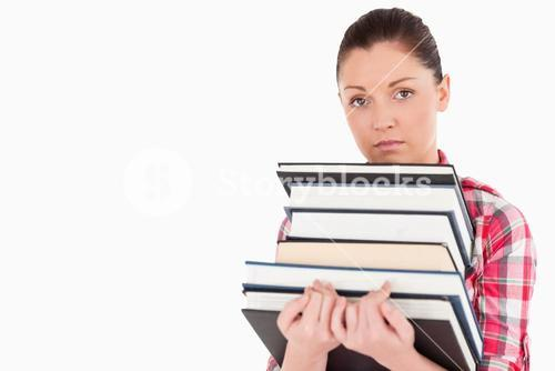 Sad female posing with books while standing
