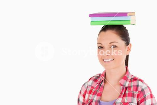 Gorgeous female holding books on her head while standing