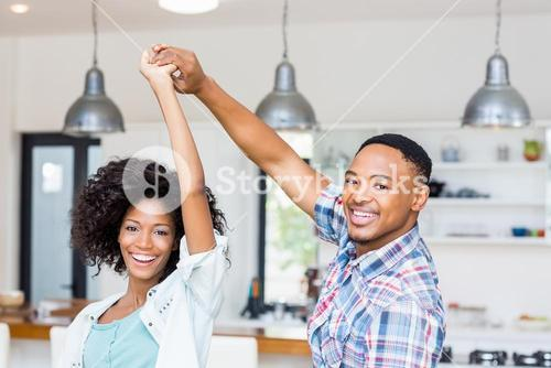 Happy couple dancing in kitchen