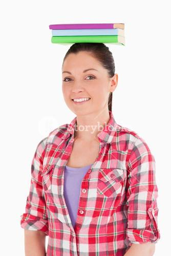 Good looking female holding books on her head while standing