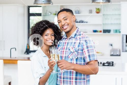 Happy couple toasting champagne glass in kitchen