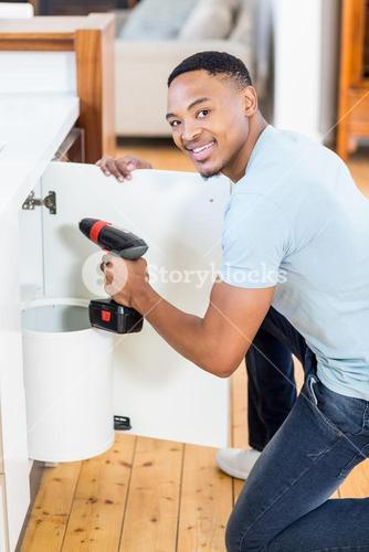 Man drilling a hole inside the cabinet