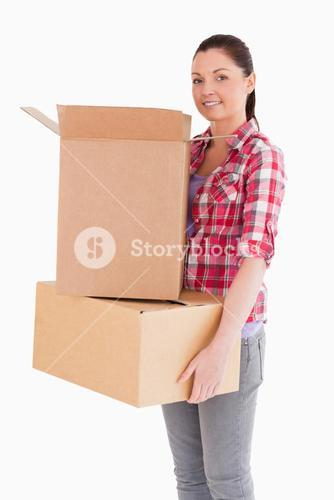 Attractive woman holding cardboard boxes while standing