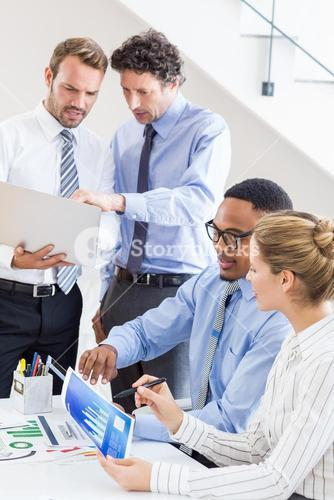 Business colleagues reviewing a report at desk