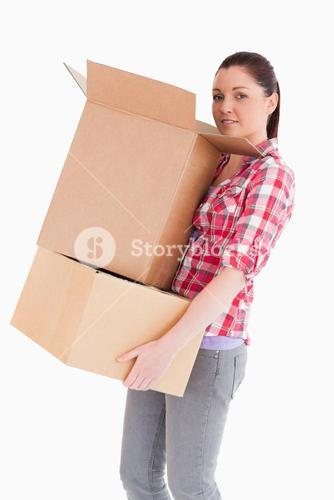Good looking woman holding cardboard boxes while standing