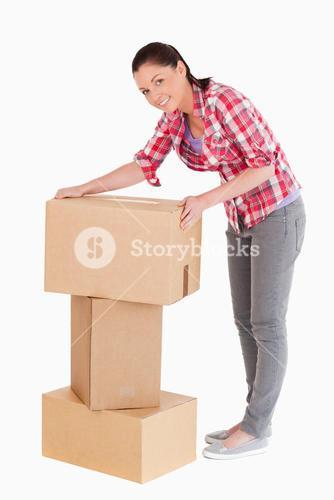 Good looking woman posing with cardboard boxes while standing