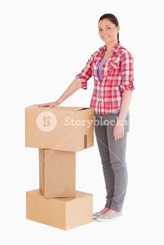 Beautiful woman posing with cardboard boxes while standing