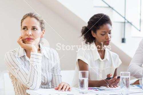 Businesswoman day dreaming while having meeting with colleagues