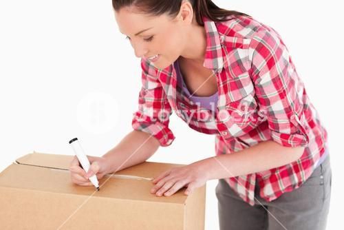Portrait of a beautiful woman writing on cardboard boxes with a marker while standing