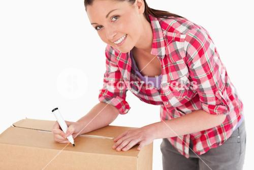 Portrait of an attractive woman writing on cardboard boxes with a marker while standing