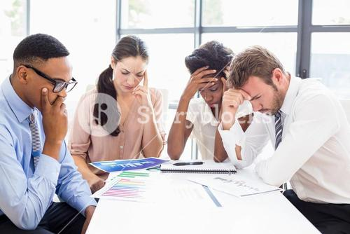 Depressed businesspeople sitting at table during a meeting