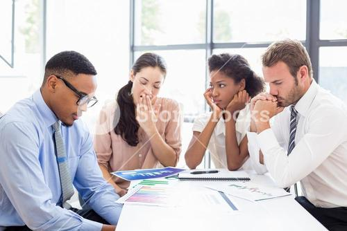 Tensed businesspeople sitting at table during a meeting