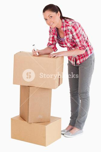 Good looking woman writing on cardboard boxes with a marker while standing