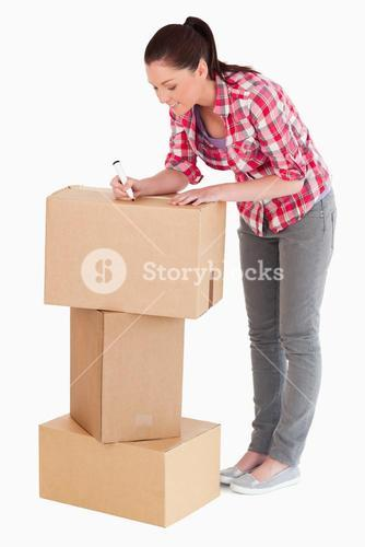 Gorgeous woman writing on cardboard boxes with a marker while standing
