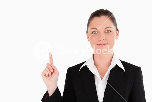 Good looking woman in suit pointing at a copy space