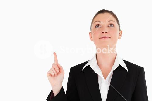 Charming woman in suit pointing at a copy space