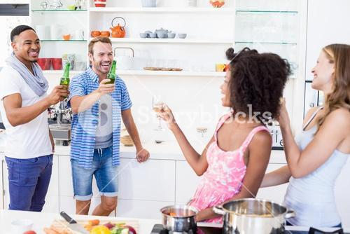 Friends toasting beer and wine in kitchen