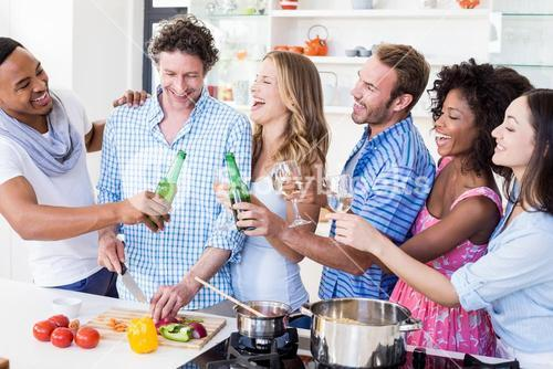 Group of friends toasting beer and wine glasses in kitchen