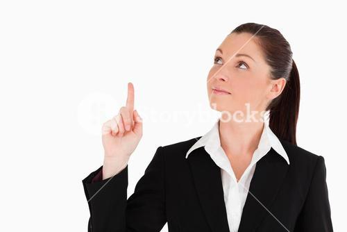 Pretty woman in suit pointing at a copy space