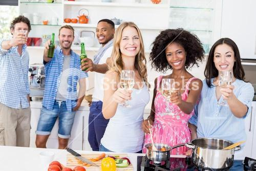 Friends toasting beer and wine glasses in kitchen