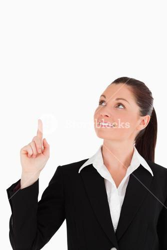 Gorgeous woman in suit pointing at a copy space