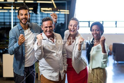 Business colleagues cheering with clenched fist