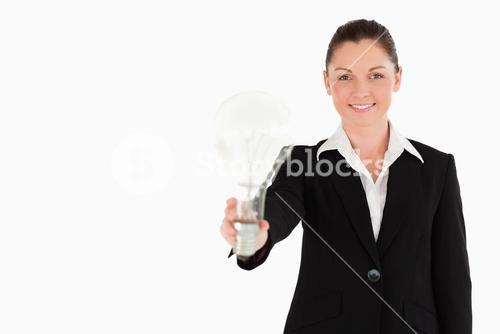 Attractive woman in suit holding a light bulb while standing