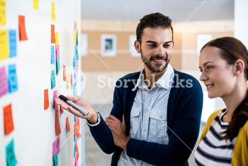 Colleagues looking at white board