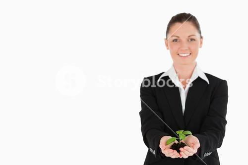 Good looking woman in suit holding a small plant